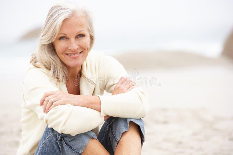 Mujer mayor el el día de fiesta que se sienta en la playa del invierno imagen de archivo