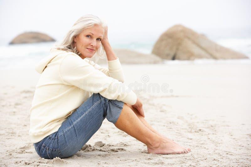Mujer mayor el el día de fiesta que se sienta en la playa del invierno foto de archivo