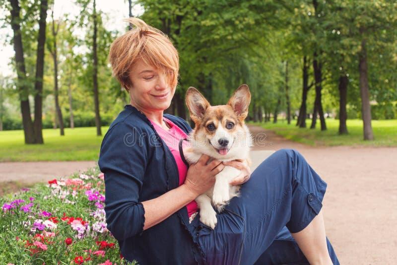 Mujer mayor elegante que abraza su animal doméstico del perro al aire libre foto de archivo libre de regalías