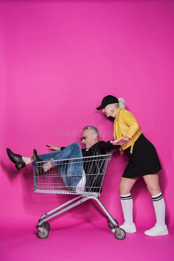 Mujer mayor elegante sonriente que empuja la carretilla de las compras con el hombre mayor alegre que se divierte imagen de archivo