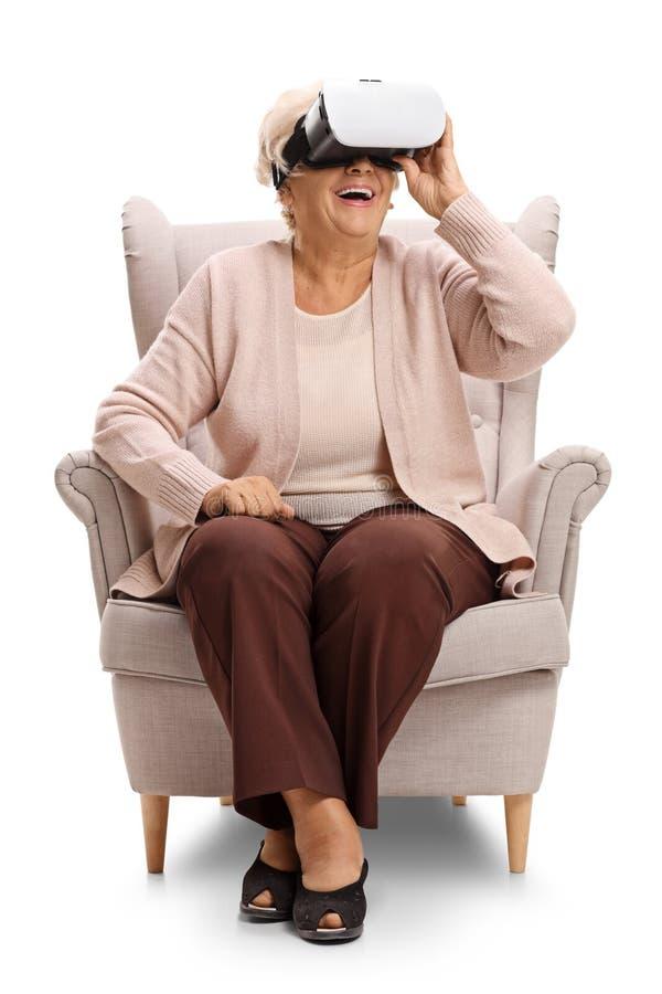 Mujer mayor emocionada que se sienta en una butaca y que usa un headseat de VR fotos de archivo