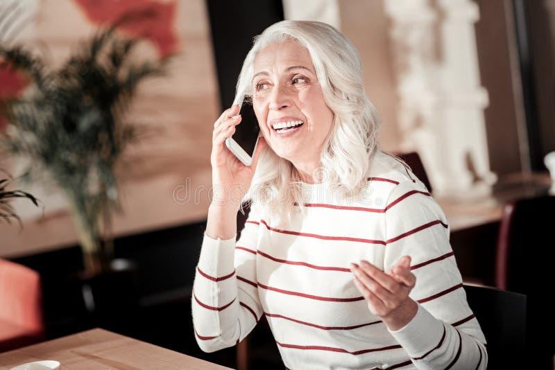 Mujer mayor emocional agradable que se sienta y que habla en el teléfono imagen de archivo libre de regalías