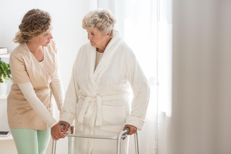 Mujer mayor en albornoz con el caminante y la enfermera útil que la apoyan imágenes de archivo libres de regalías
