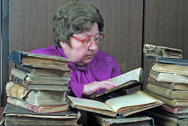 Mujer mayor en biblioteca foto de archivo libre de regalías