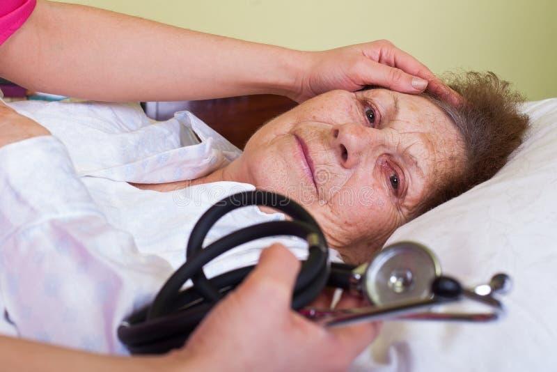 Mujer mayor en cama fotos de archivo