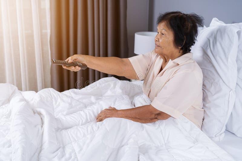 Mujer mayor en cama con la TV teledirigida y de observación fotografía de archivo libre de regalías