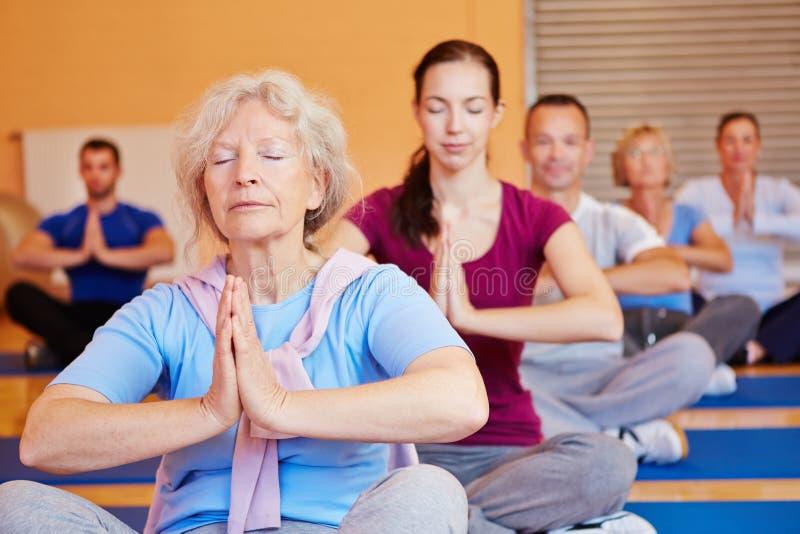 Mujer mayor en clase de la yoga en gimnasia fotografía de archivo libre de regalías