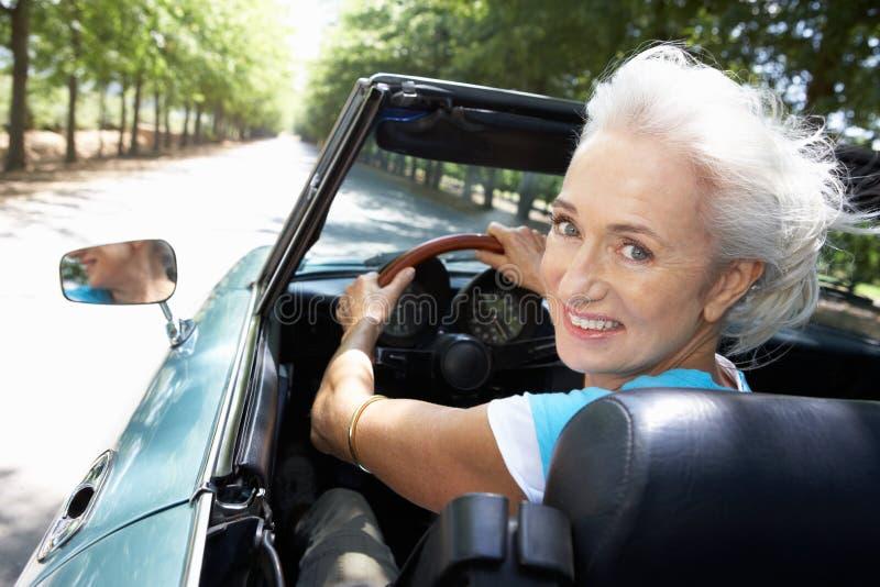 Mujer mayor en coche de deportes imagen de archivo