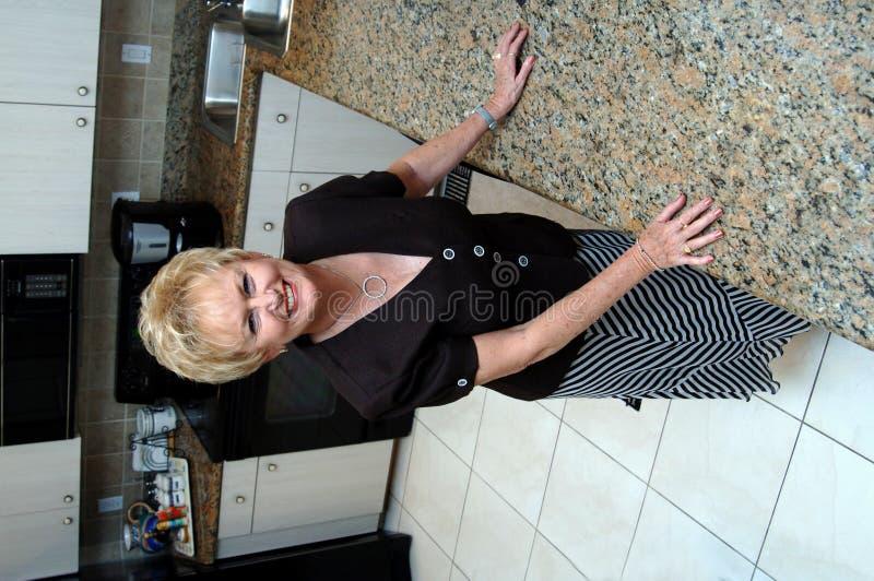 Mujer mayor en cocina fotografía de archivo