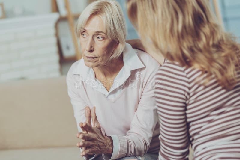 Mujer mayor en cuestión que mira en la distancia imagen de archivo libre de regalías