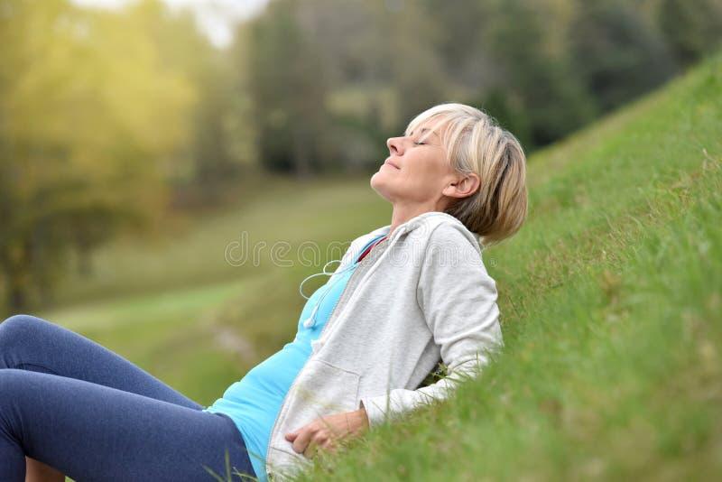Mujer mayor en el equipo que activa que miente en hierba foto de archivo