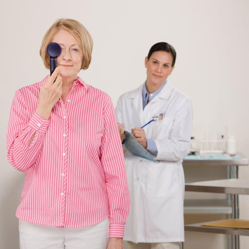 Mujer mayor en el examen de ojo fotografía de archivo