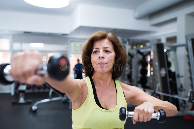 Mujer mayor en gimnasio que se resuelve con los pesos foto de archivo