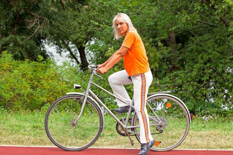 Mujer mayor en la bicicleta imágenes de archivo libres de regalías