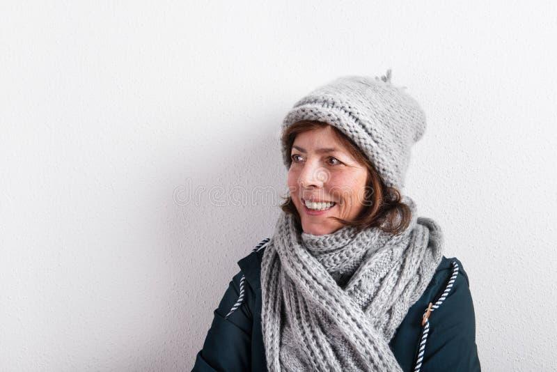 Mujer mayor en la bufanda y el sombrero de lana, tiro del estudio foto de archivo libre de regalías