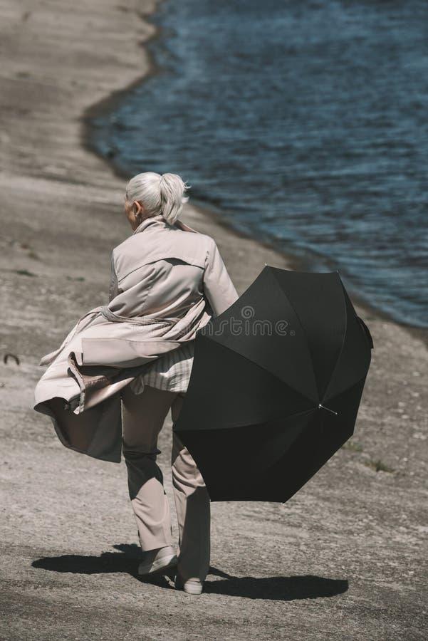 Mujer mayor en la capa que sostiene el paraguas negro y que camina en la orilla fotos de archivo