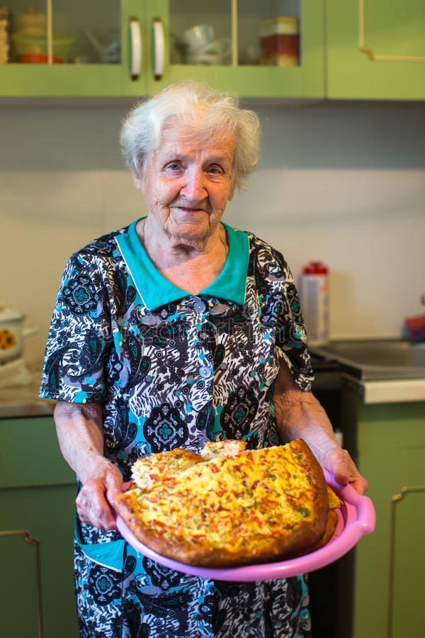 Mujer mayor en la cocina con una empanada en sus manos manía imágenes de archivo libres de regalías