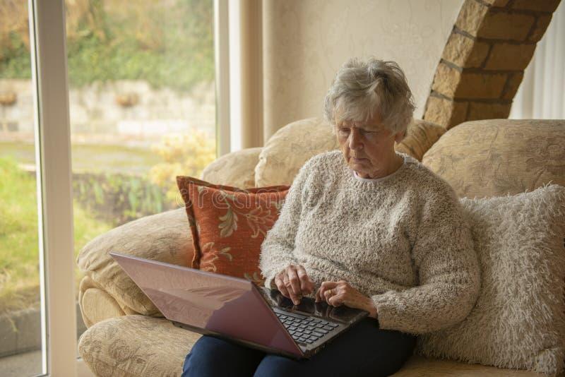 Mujer mayor en la computadora portátil imagen de archivo libre de regalías