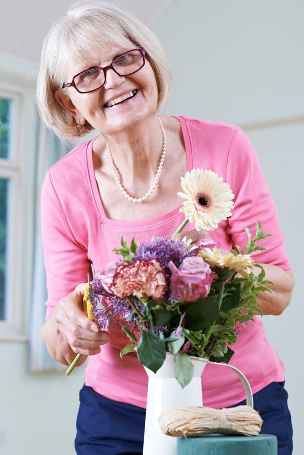 Mujer mayor en la flor que arregla la clase foto de archivo