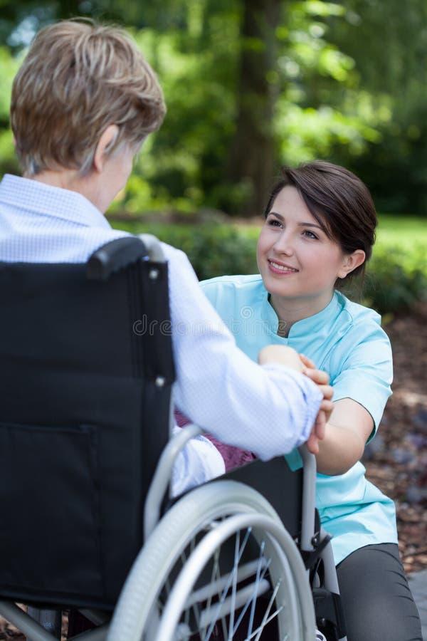 Mujer mayor en la silla de ruedas con su cuidador fotos de archivo
