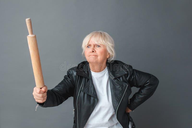 Mujer mayor en la situación del estudio de la chaqueta de cuero aislada en gris con el rodillo que amenaza alguien enojado fotografía de archivo