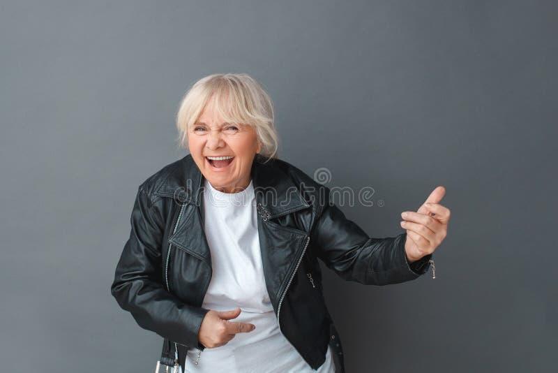 Mujer mayor en la situación del estudio de la chaqueta de cuero aislada en la guitarra imaginaria que juega gris que ríe el prime imagenes de archivo