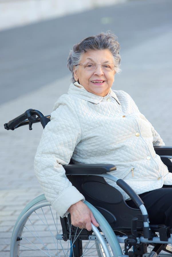 Mujer mayor en la sonrisa de la silla de ruedas foto de archivo