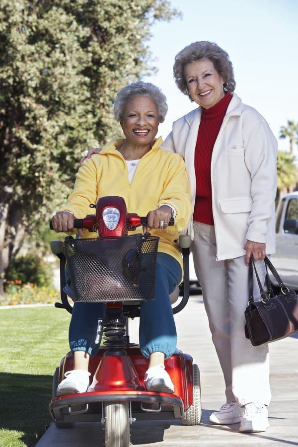 Mujer mayor en la vespa de motor con el amigo fotos de archivo libres de regalías