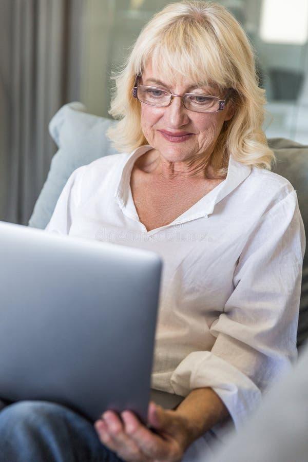 Mujer mayor en lentes usando el ordenador portátil fotos de archivo libres de regalías
