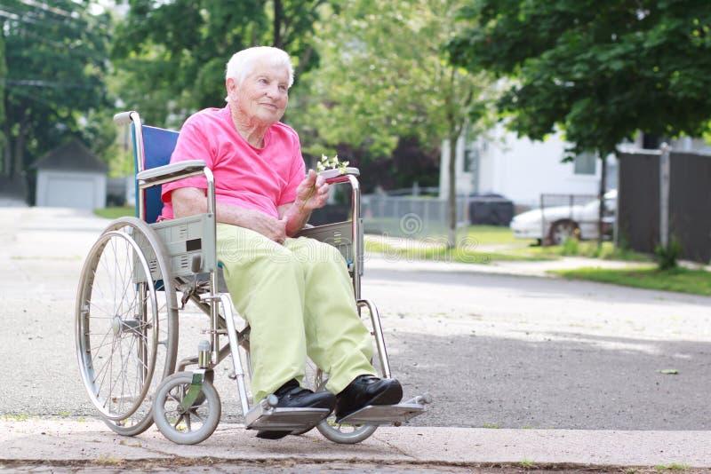 Mujer mayor en sillón de ruedas imágenes de archivo libres de regalías