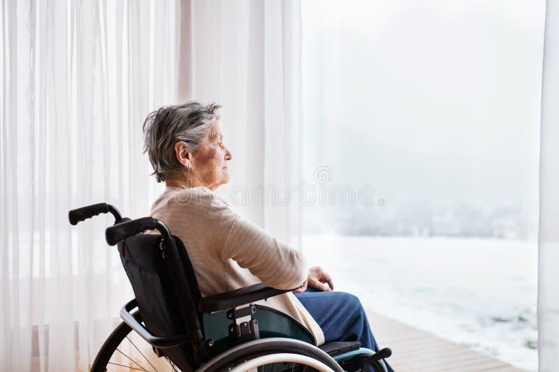 Mujer mayor en silla de ruedas en casa imágenes de archivo libres de regalías