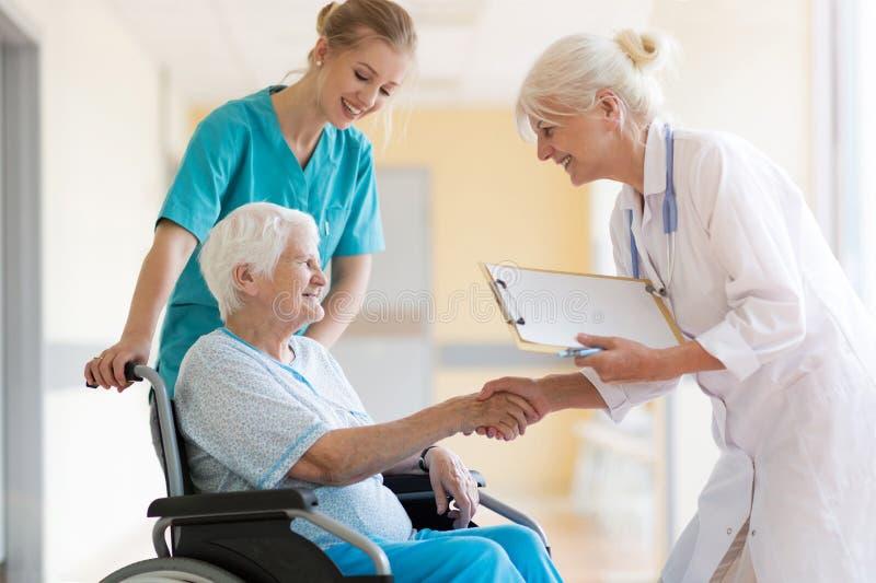 Mujer mayor en silla de ruedas con el doctor de sexo femenino en hospital imagen de archivo