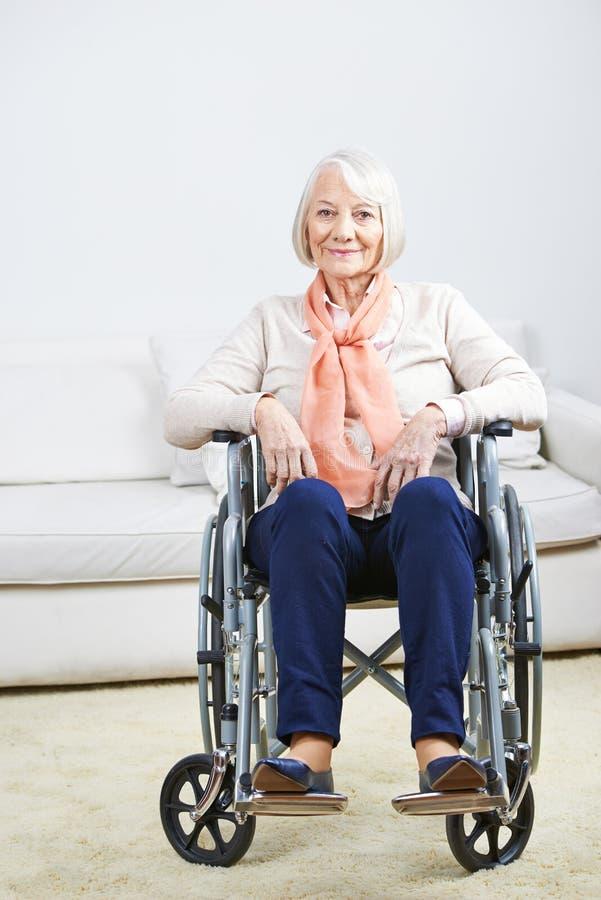 Mujer mayor en silla de ruedas en casa fotografía de archivo