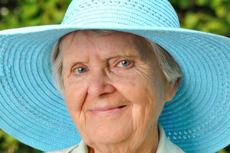 Mujer mayor en sombrero azul. imagenes de archivo