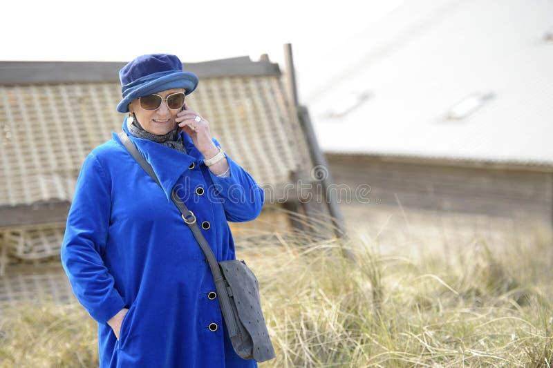 Mujer mayor en su teléfono celular imagen de archivo libre de regalías