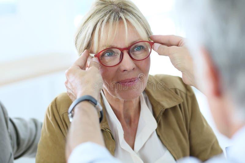 Mujer mayor en tienda óptica fotos de archivo