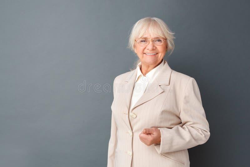 Mujer mayor en traje fromal y los vidrios que colocan el estudio en la cámara de mirada de presentación gris alegre imagen de archivo libre de regalías