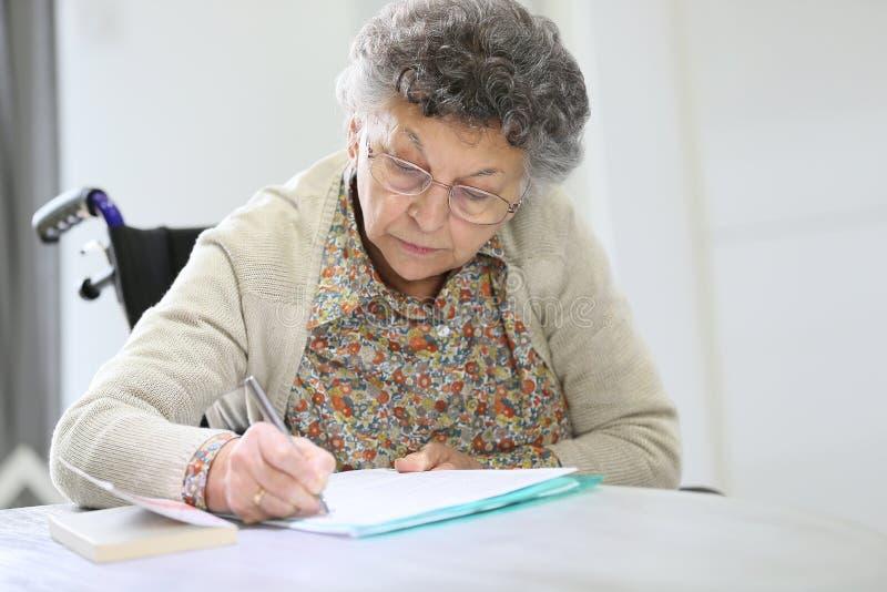 Mujer mayor en una silla de ruedas que anota notas fotos de archivo