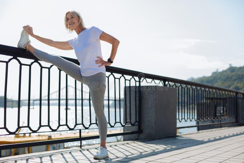 Mujer mayor encantadora que estira cerca de la barandilla del puente fotos de archivo