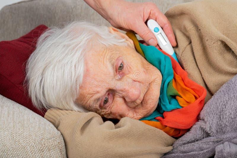 Mujer mayor enferma - fiebre imagenes de archivo