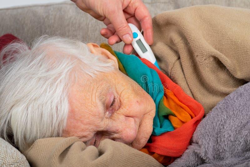 Mujer mayor enferma - fiebre fotos de archivo