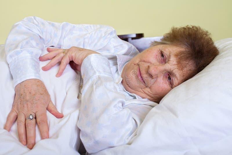 Mujer mayor enferma que miente en cama fotos de archivo