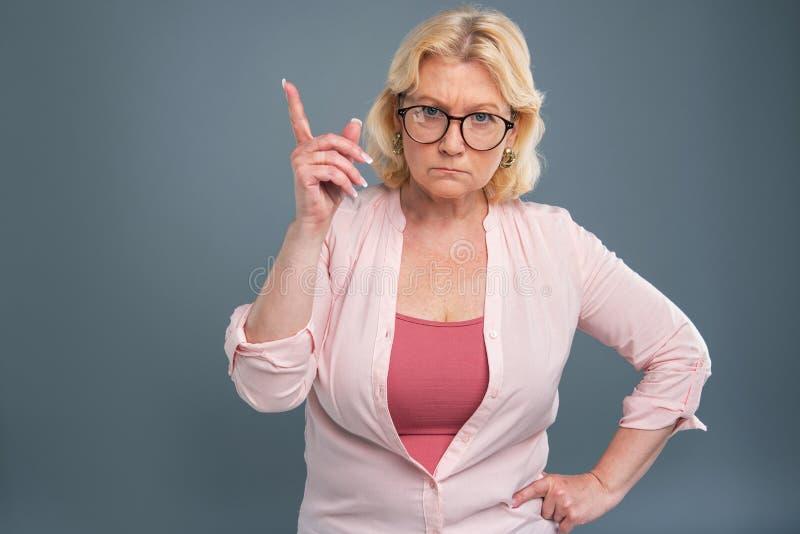 Mujer mayor enojada que está a punto de regañar alguien imagen de archivo libre de regalías