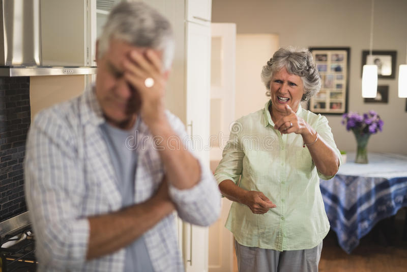 Mujer mayor enojada que grita en hombre mayor imagen de archivo