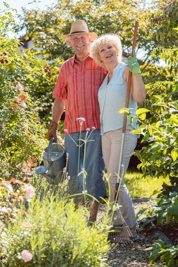 Mujer mayor feliz activa que se coloca al lado de su marido fotografía de archivo