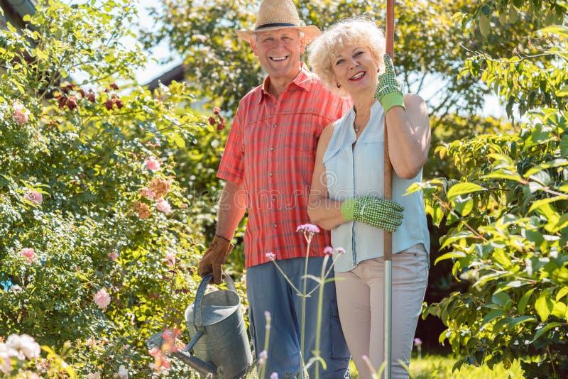 Mujer mayor feliz activa que se coloca al lado de su marido durante trabajo del jardín imagen de archivo