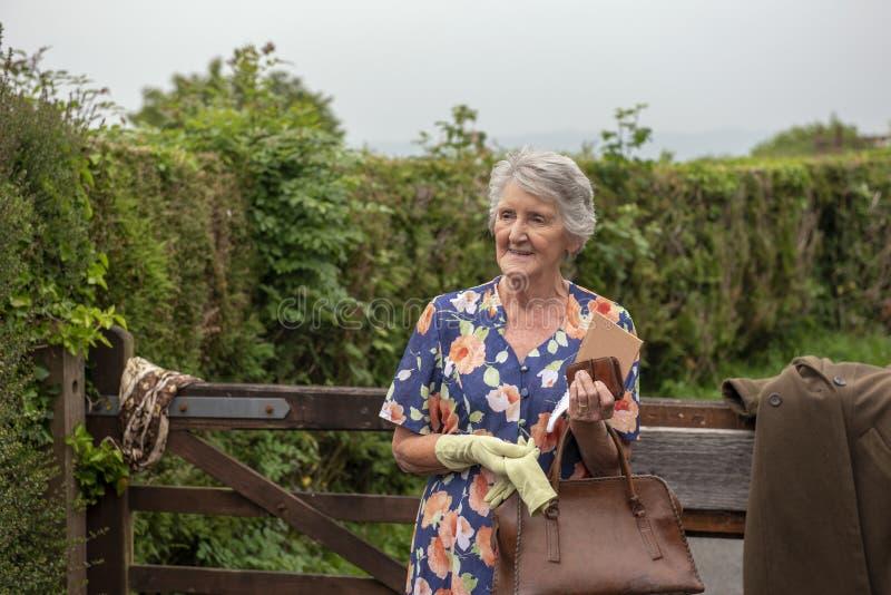 Mujer mayor feliz al aire libre por una vieja puerta de madera imagenes de archivo