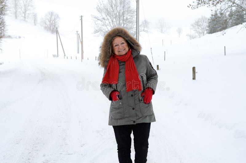 Mujer mayor feliz amistosa que se coloca en nieve imágenes de archivo libres de regalías