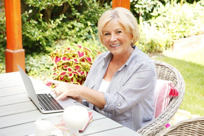 Mujer mayor feliz con la computadora portátil fotos de archivo