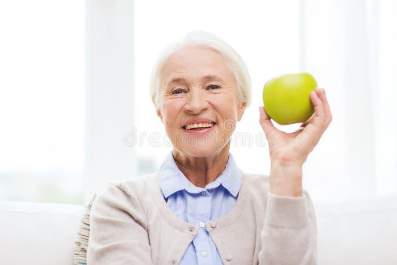 Mujer mayor feliz con la manzana verde en casa fotografía de archivo